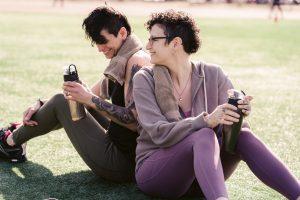 sportswomen drinking water on grass