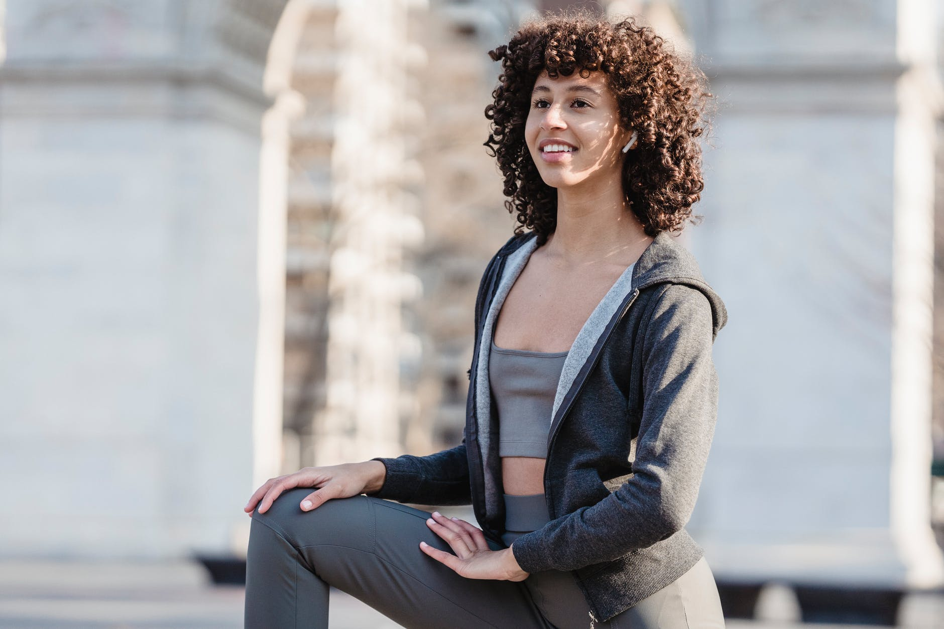 positive ethnic woman doing lunge exercise for stretching legs
